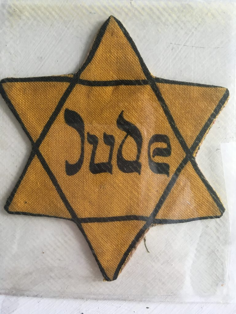 "Yellow Star of David inscribed with the word ""Jude"" for Jew"